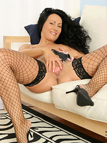 Fiery hot brunette cougar wearing fishnets spreads her honey filled pussy