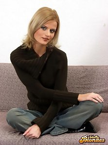 Naughty blonde goddess stripping her tight jeans on the couch