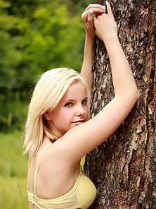 Very pretty and naked teenager is hugging a tree outdoors