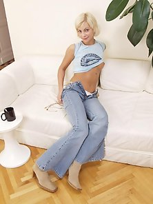 Sweet blonde babe in jeans strips on white couch