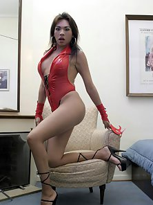 Slutty shemale in red latex lingeria strips and shows her big cock