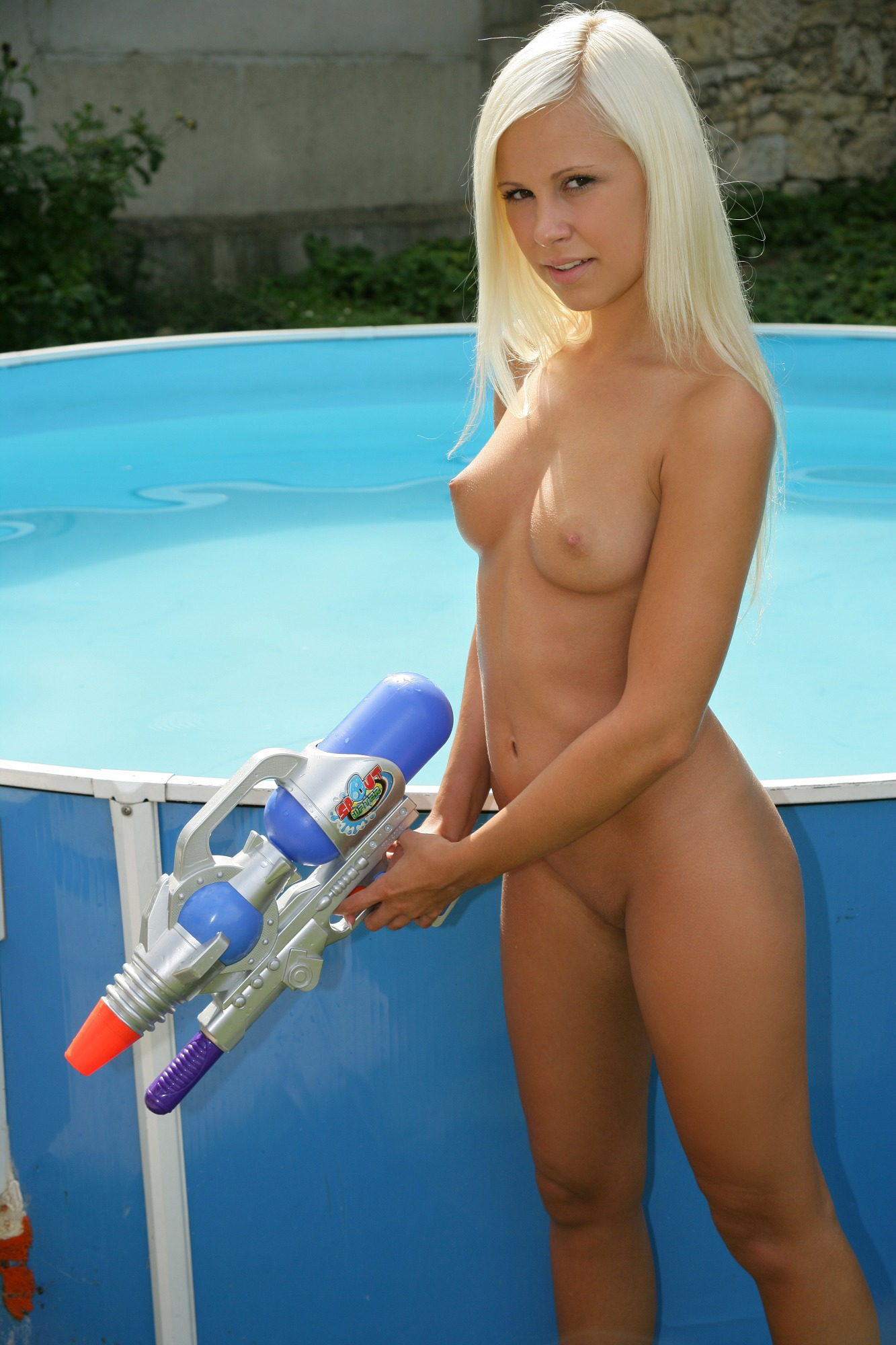 Blonde babe takes a naked swim in her pool - Movie Shark