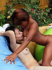 An interracial lesbian couple fisting each other outside