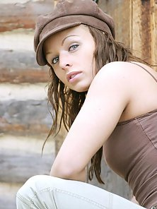 Brunette Wearing Cap Posing Undressed with Logs