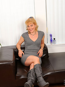 Elegant Anilos milf in boots slips off her sexy dress revealing her bra and sheer thongs