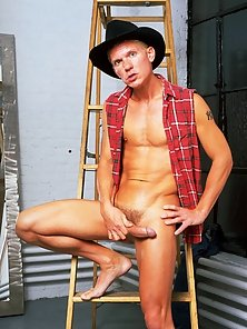 Tanned stud with a cowboy hat posing for the camera