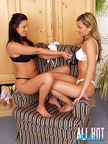 Two tawny lesbian cuties sharing a fat golden dildo on the couch