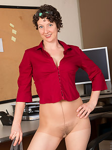 Brunette milf strips down in her office and massages her wet pussy