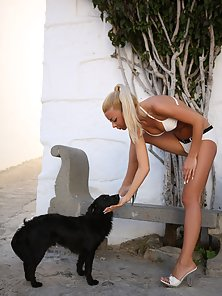 Cute and sexy blonde posing fully nude with dog outdoors