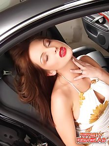 Arousing red haired chick fingering her yummy pussy in a luxury car