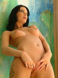Hot brunette baring all by the painting on the wall