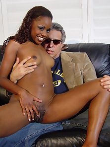Sexy black beauty posing with older guy on couch