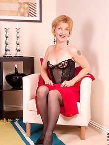 Hot sexy cougar in black lingerie masturbates with a stiff glass dildo on the floor